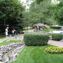 manicured course showing water feature, flower bed and gazeebo