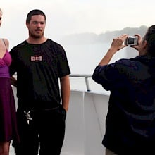 With the Horseshoe Falls in the background, Heather Schaloux and Donovan Conlon pose for a picture aboard Hornblower Niagara's first-ever Sunset Cocktail cruise as Hornblower employee Eveline Szabo helps them preserve the memory. Photo: Corey Larocque