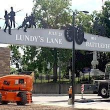 With the Battle of Lundy's lane memorial monument behind them, workers put in place a new sign that spans the historic street. The sign pays tribute to the 1814 Battle of Lundy's Lane, a pivotal event in the War of 1812. The new sign is part of the city's effort to commemorate the war's bicentennial. Photo: Corey Larocque